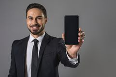 Happy smiling young man presenting smartphone stock photos