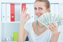 Portrait of attractive cheerful female showing many banknotes of one hundred dollars on the office background. Winning money prize concept Royalty Free Stock Photo