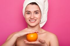 Portrait of attractive cheerful woman with white towel on head, holds orange over pink background. Young smiling female visits spa royalty free stock photo