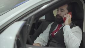 Portrait attractive confident bearded businessman sitting in the vehicle and inspects newly purchased auto from the car. Successful businessman inspects newly stock video