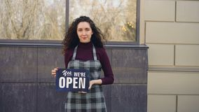 Portrait of attractive confident woman in apron small business owner holding `yes we are open` sign standing outside and