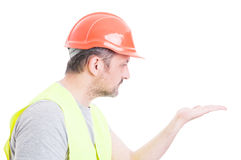 Portrait of attractive constructor looking at his palm Stock Photo