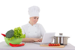 Portrait of attractive cook woman in uniform sitting at the kitc Royalty Free Stock Photos
