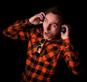 Crazy young and handsome man with headphones and modern sunglasses in stylish checkered shirt with hands on headphones stock image