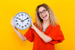 Woman in dress with clocks. Portrait of attractive curly-haired woman in red dress and eyeglasses isolated on orange background holding clocks and showing her Stock Photos