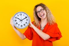 Woman in dress with clocks. Portrait of attractive curly-haired woman in red dress and eyeglasses isolated on orange background holding clocks and showing her Royalty Free Stock Images