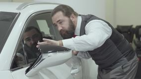 Portrait attractive cute confident bearded businessman in a business suit inspects newly purchased auto from the car. Successful businessman inspects newly stock video footage