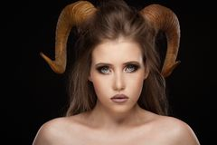 Portrait of an attractive demon woman with horns. And curly hair, studio shot for Halloween stock photography