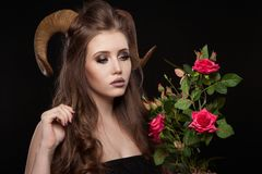 Portrait of an attractive demon woman with horns. And curly hair, synthetic flowers, studio shot for Halloween royalty free stock image
