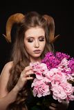 Portrait of an attractive demon woman with horns. And curly hair, synthetic flowers, studio shot for Halloween stock photo