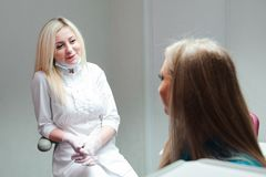 Portrait of attractive dentist talking to her patient at clinic stock photos