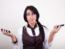 Portrait of attractive dissatisfied businesswoman. With phones in hands Royalty Free Stock Image