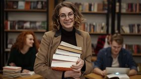 Portrait of attractive european girl student holding books in high school library smiling looking at camera. Education