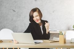 Win lottery concept. Portrait of attractive european woman celebrating success at modern office desk with laptop. Win lottery concept Stock Photo