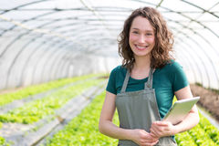 Portrait of an attractive farmer in a greenhouse using tablet Royalty Free Stock Photos