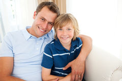 Portrait of an attractive father hugging his son. On the sofa Royalty Free Stock Photography