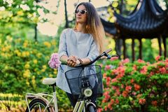 A woman with city bicycle near traditional chinese pavilion in a park. Portrait of attractive female with city bicycle near traditional chinese pavilion in a Royalty Free Stock Image