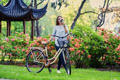 A woman with city bicycle near traditional chinese pavilion in a park. Portrait of attractive female with city bicycle near traditional chinese pavilion in a Stock Image