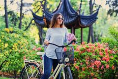 A woman with city bicycle near traditional chinese pavilion in a park. Portrait of attractive female with city bicycle near traditional chinese pavilion in a Stock Photo