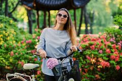 A woman with city bicycle near traditional chinese pavilion in a park. Portrait of attractive female with city bicycle near traditional chinese pavilion in a Stock Images