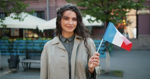 Portrait of attractive female student standing outside with French national flag. Smiling looking at camera on windy summer day. People and patriotism concept stock video