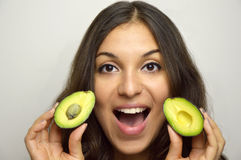 Portrait of attractive girl with avocado healthy fruit stock photography
