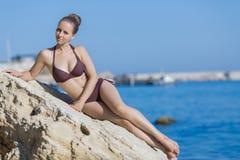 Portrait of attractive girl on rocky beach Stock Photos