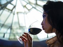 Portrait of an attractive girl with beautiful lips who drinks red wine from a glass royalty free stock image