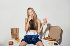 Portrait of attractive girl with blonde hair in sport top and shorts sitting on table with big amount of unhealthy food Royalty Free Stock Photo