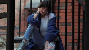 Portrait of an attractive girl in a blue coat. young fashionable woman stock video