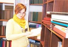Portrait of attractive girl book against bookshelves. Stock Photo