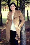 Portrait of an attractive girl in a coat on nature. beautiful woman stands next to a tree in a coat. stock images