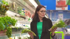 Portrait attractive girl with is faced with a choice of what to buy in the Department with vegetables in the supermarket. Attractive girl with glasses is faced stock video