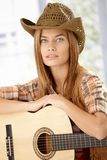 Portrait of attractive girl with guitar. And western hat Stock Photography