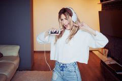 Young beautiful woman music lover. Portrait of attractive girl in headphones with phone, apps for listening to music Royalty Free Stock Photos