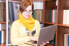 Portrait of attractive girl with laptop against bookshelves. Royalty Free Stock Photography