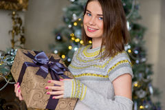 Portrait of attractive girl in pullover holding gift box Royalty Free Stock Photos