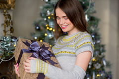 Portrait of attractive girl in pullover holding gift box Royalty Free Stock Images