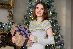 Portrait of attractive girl in pullover holding gift box Stock Photos