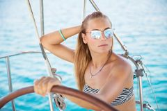 Attractive girl on sailboat. Portrait of an attractive girl on sailboat, wearing stylish sunglasses and bikini,  luxury summer vacation on the sea, active Stock Images