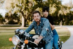 Portrait of Attractive Good Looking Young Modern Trendy Fashionable Guy Girl Couple Riding on Green Motorcycle Cruiser Old School royalty free stock photos
