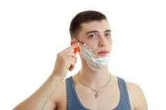 Portrait of an attractive guy with foam on his face which looks into the camera and shaves Stock Photos
