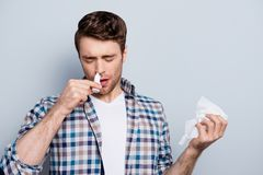 Portrait of attractive guy with a nasal spray and tissue in hand. S, using nose drops over grey background, concept of treatment for allergies or the common cold Stock Photos