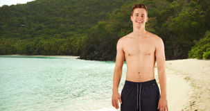 Portrait of attractive guy standing shirtless in swim shorts on Caribbean beach. Stock Photography