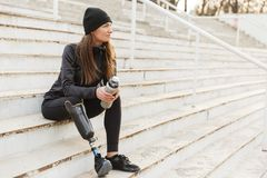Portrait of attractive handicapped woman in black tracksuit with. Prosthetic leg sitting at the street stairs and holding thermos cup royalty free stock images