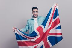 Portrait of attractive, handsome man in glasses and jeans shirt. Holding waving Jack Union flag Stock Images