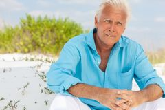 Portrait of Attractive Handsome Senior Man on Beach. Portrait of a worried concerned thoughtful attractive handsome senior man sitting down outside on a beach Stock Image