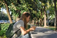 Portrait of attractive happy asian woman holding smartphone while sitting on roadside at the city street. royalty free stock images