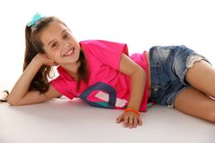 Portrait of an attractive happy brunette little girl with bare legs smiling. Portrait of a lying attractive young brunette schoolgirl in denim shorts and a Stock Photos