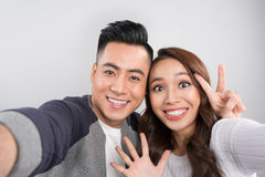 Portrait of attractive happy man and woman in love making selfie Royalty Free Stock Image